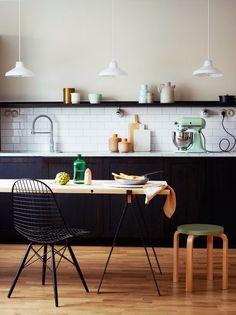 black lower cabinets, light wood floors, white subway tile and single shelf. pendant lighting in kitchen.