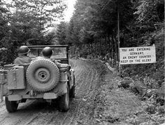 """""""Welcome to Germany"""", reads this sign as a couple of GI's drive this Willys Jeep ~"""
