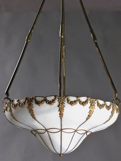 "Circa 1910, the Leaded Glass Inverted Dome with Floral Relief has 12 panels, garland and swag design and stylized husks on rods. 38"" drop x 19"" diameter x 7 1/2"" shade depth. Drop can be adjusted. $4730.00 SOLD"