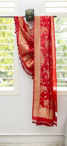 This Benares silk dupatta is in cherry red with a floral pattern in gold zari. The border and pallu are in gold zari with a cherry red edge making it perfect for a lehenga or a salwar kameez