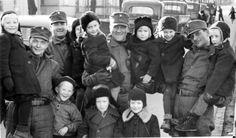 Finnish child evacuees with soldiers. Date and place unknown. Need a translation for caption: Evakot joutuivat majoittumaan vieraiden ihmisten asuntoihin selvitäkseen talven yli. Pääosin evakot otettiin lämpimästi vastaan    Sekasorron keskellä perheenjäsenet joutuivat eroon toisistaan, ja vaikka monet lopulta työn ja tuskan jälkeen löysivät toisensa, ei kaikille selvinnyt koskaan, mitä läheisille oli tapahtunut.