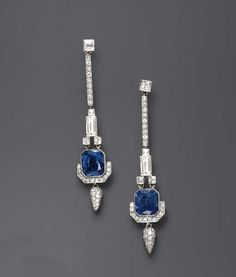 A PAIR OF DIAMOND AND SAPPHIRE EAR PENDANTS   Each square-cut diamond, suspending a circular-cut diamond line, to the square and baguette-cut diamond link, terminating in a rectangular-cut sapphire, weighing approximately 4.91 and 4.59 carats, enhanced by circular-cut diamond trim and a pavé-set diamond drop, mounted in platinum, in a red leather case. Art Deco or Art Deco style.