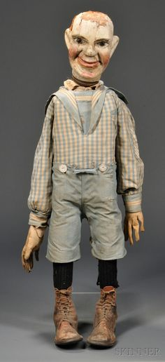 Ventriloquist's Dummy, early 20th century, carved and painted wooden head, mounted on a removable turned handle, with glass eyes, jointed jaw with kid leather covered chin, wood frame body, wearing a child's cotton sailor suit, jersey gloves, and leather shoes, (hair loss, minor joinery separation), ht. approx. 37 in.