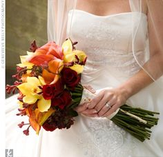 calla lilies, orchids, and roses in autumn hues.