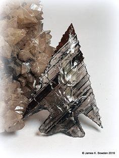Triflow Obsidian Elko Eared Atlatl Dart Point flintknapped by James K. Bowden.  Point rests on Dogtooth Calcite.  http://www.Flintknappers.com/gallery/past2present #arrowhead #atlatl #elko #elkoeared #calcite #crystals #flintknap #Nativeamerican #obsidian