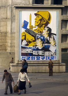 A couple hefts a heavy sack across the road (no cart), while another man engages a soldier/policeman in conversation. Maybe hes being questioned? South Korea North Korea, Inside North Korea, The Rok, Military First, Propaganda Art, Asia, Korean Peninsula, Korean People, Korean War