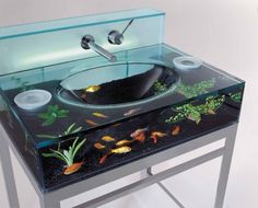 Yeah! I want one in each bathroom! ~ Fish swimming inside your bathroom sink! In case you were wondering: you're able to add and remove plants and fish by lifting the top glass plate and feeding can be done through one of the circular holes on the sides. Source: Opulent Items.