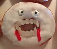 """Easy, Cute, Halloween Treat for my son's 4th Grade Class Halloween Party! Donuts with vampire teeth, candy eyes and a little """"blood"""" red icing added!  I think it would look better with different colored vampire teeth (Just my opinion)"""
