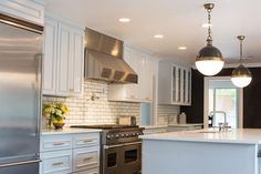 Fantastic kitchen features light gray cabinets painted Sherwin Williams Gray Screen accented with gold hardware paired with white quartz countertops and a white subway tiled backsplash accented with dark grout.