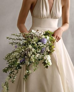 Delicate branches add structure and drama to this lush cascading bouquet