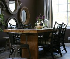 large reclaimed wood table with different chairs ... like the mirrors on the wall .. cute idea