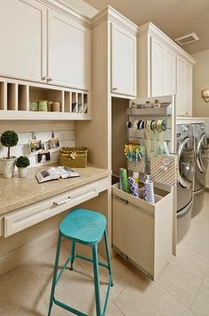 Craft room in laundry room features a built-in desk paired with a turquoise metal stool under ...