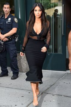Femme fatale: Kim Kardashian dazzled in a sheer black blouse and fishtail skirt as she left her NYC apartment on Monday
