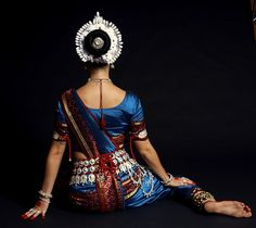 Indian woman in costume for traditional dance with ornaments. back view
