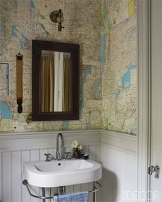 A guest cottage bath papered with old AAA maps; the wainscoting is painted in Farrow & Ball's Cornforth White