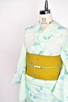 透き通ったミントグリーンに、絣織り風に染め出された蝶々と幾何学パターンが愛らしい化繊の夏着物です。