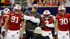 Former Wisconsin defensive end J.J. Watt posses for a pictures with Kenzel Doe (3), Konrad Zagzebski (91) and Derek Landisch (30) before an NCAA college football game Saturday, Aug. 30, 2014, in Houston. (AP Photo/David J. Phillip)