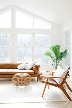 Bright white living room with Mid Century Modern furniture and camel leather sofa.