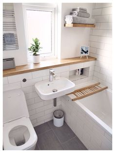 Simple bathroom of white and wood with grey tiles/accents.