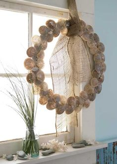 Clamshells give a store-bought wreath nautical personality. Wrap a 14-inch wreath in 1⁄2-inch neutral-hue grosgrain ribbon. Attach the shells with hot glue, placing some end-to-end as if the clams are open. A knot of gauzy burlap creates a textural hanger. Matthew's Secrets Display the wreath as part of a sea-inspired composition with spiky coral, sea oats, and stones.