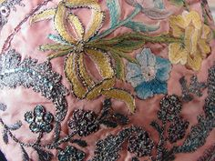 Detail embroidery, child's bonnet, 18th century. Pink silk embroidered with floral bouquets tied with ribbons, meandering leaves and flowers worked in metallic threads and tiny sequins with a wider metallic fringe border around the edge.