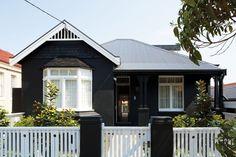 Black House. Bungalow pintado de negro mate con detalles blancos en Australia.