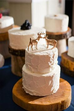 A two-tier winter wedding cake with deer cake toppers | Brides.com