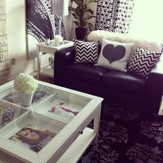Black furniture with accent pillows. Chevron and heart print. Eiffel tower print in background. Quad section coffee table.