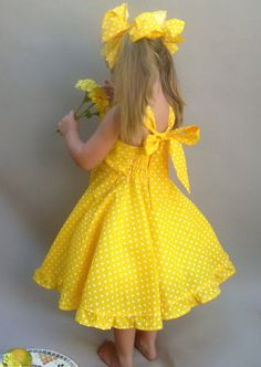 A beautiful dress made with yellow and white polka dot fabric. The sleeveless shoulder straps ties at the back with a big bow. This dress pattern has a fully lined bodice and no buttons or zippers!  Bright as a Spring day, this pretty twirly skirt dress will make your little girl stand out in the crowd.  Back bodice has elastic casting for a very easy on and off. This is especially appreciated when dressing the younger ones. Skirt is extra full for twirling and twirling! The dress was fitted…
