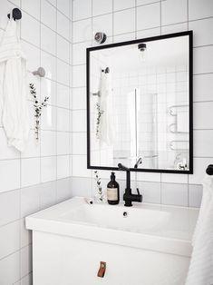 'Simpele' Scandinavische badkamer in zwart wit kleuren. Door het all-white thema spreekt de zwarte spiegel nóg meer.