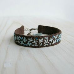 This bohemian style cuff bracelet has teal ombre flowers hand embroidered on brown linen, it has a lobster clasp closure and is finished with a little