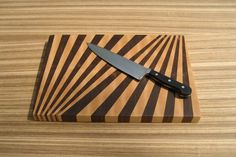 This end-grain cutting board is made up of two fan-like patterns, giving the impression of a double rising sun. Unlike most of the items I make, this cutting board is not inspired by any gamer nostalgia or other geekery...I just thought it was a pretty cool design. The board is made of walnut and hard-maple, put together with FDA approved, water-proof glue, and treated with a mixture of mineral oil and beeswax. End-grain cutting boards like this one are very durable and will...