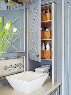 Bathroom Vanity with Corner Storage - In a small bath, every inch counts. Take advantage of an otherwise wasted corner by installing custom cabinets designed for the space. Here, a built-in corner cabinet holds baskets with grooming supplies and towels where they are needed next to the sink. The muted blue cabinet door matches the cabinets below the sink for a cohesive look.