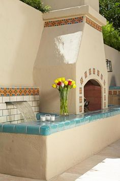 Stucco Fireplace and Water Feature Trimmed With Spanish Tile A stucco outdoor fireplace and water feature is trimmed with ceramic tiles featuring Spanish-style patterns and tiles in a beautiful turquoise color for a soothing fire-and-water combination. Spanish Pool, Spanish Courtyard, Spanish Tile, Mexican Courtyard, Stucco Fireplace, Backyard Fireplace, Fireplaces, Fireplace Outdoor, Fireplace Ideas