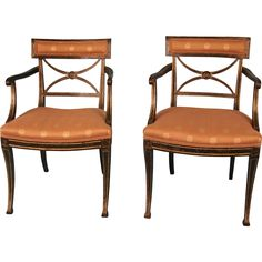 A matched pair of Regency paint and parcel gilt armchairs, the upholstered crest rail above an X frame splat centered with a boss, the saddle seats