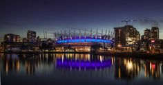 cityscape with BC Place stadium - the sun has just set beyond the stadium to create a surreal glow over downtown Vancouver from False Creek. Bc Place, Downtown Vancouver, Football Pictures, Cityscapes, Marina Bay Sands, New York Skyline, Swimming Pools, Cities, Glow