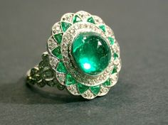 Emerald and Diamond Ring Platinum, set to the center with one cabochon emerald bordered by assorted small round diamonds and calibre-cut emeralds, signed Tiffany.