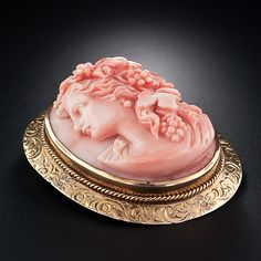 Bacchus Coral Cameo Brooch / The young and effeminate Greek and Roman god of wine and revelry is elegantly depicted in high-relief and sporting his grapevine tresses in this ravishing Victorian cameo handcarved in bright, peachy-salmon coral.