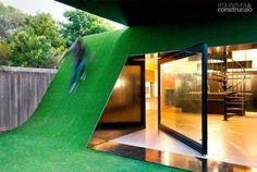 Extensão do jardim, a grama artificial na fachada curva, com inclinação de 50…