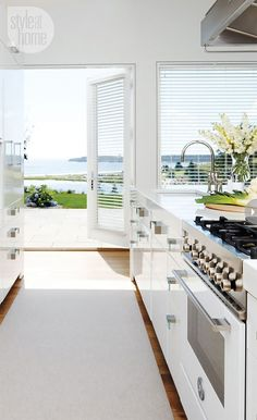 Kitchen Dreams. White with an door open to the outdoors.
