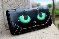 This black cats eyes purse with a little ear detail is an absolutely mesmerizing fashion accessory. The purse zips all the way round and has a generous amount of space inside. Twelve card slots are located on both internal walls with the patterned coin compartment and three sections for notes in the middle. Plenty of room, even for the most demanding users, offers great functionality but it's the unique design your friends will be jealous of!