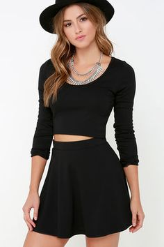 """On your way out of this atmosphere, make sure you grab the Stratosphere Black Two-Piece Skater Dress! Medium-weight stretch knit fabric lays across a fitted and cropped long sleeve bodice with a scoop neckline and darting. Matching skater skirt begins at a banded waist before flaring to a mini-length hem. Top is unlined; skirt is lined. Small top measures 15.5"""" long. Small bottom measures 14.5"""" long. 67% Viscose, 28% Nylon, 5% Spandex. Hand Wash Cold. Made With Love in the U.S.A."""