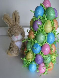 Easter Egg Tree  Please follow link for actual instructions.  What I did: Made this using a 12 inch foam cone from JoAnn and almost 96 glitter foam eggs from the Dollar Tree.  It is awesome!