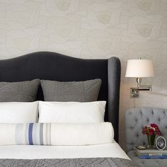 Pretty bedding and wallpaper accent wall.
