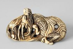An interesting ivory netsuke of a two-horned dragon. 18th/early 19th century. Winding through waves with flames emanating from his joints and three claws to the feet. Strong amber-coloured patina to the reverse