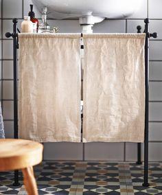 Nahaufnahme eines Vorhangs aus LENDA Meterware in Beige vor einem Waschbeckenregal