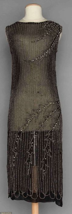 Beaded Black Flapper Dress. Silk chiffon, vertical rows of crystal beads top to hem & 2 sets of 3 curved branches outlined in beads w/ rhinestones . Augusta Auctions