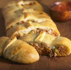 Favorite pizza toppings are wrapped inside pizza crust dough and baked, then served with additional sauce