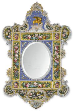 "Mosaic and blown glass mirror, Venice, attributed to Salviati and Co, late 19th c, inlaid with numerous floral sprays and garlands in a multitude of colors on a gold mosaic ground, four masks at the corners, the foliate spandrels surrounding the oval plate inlaid on a deep blue mosaic ground, the crest inlaid with the Lion of Saint Mark, the lower edge bearing inlaid banner ""Venezia"", the edges all applied with blown glass scrolls and flowerheads, 225 cmx135 cm, Sotheby's"