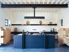 Globally-Inspired Kitchen Design | A steel H-beam—inspired by the architecture of an ancient Burgundian barn, now part of a boutique hotel—became the design motif for this kitchen. Roderick Vos copied its look to make a shelf for glasses and to anchor the room's most dramatic element: the pot rack over the island.